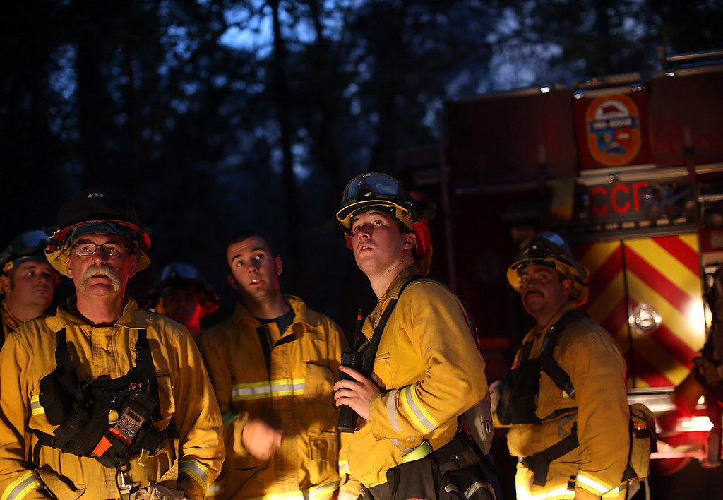 . GROVELAND, CA - AUGUST 21:  Firefighters from Ebbetts Pass Fire District monitor a back fire while battling the Rim Fire on August 21, 2013 in Groveland, California. The Rim Fire continues to burn out of control and threatens 2,500 homes outside of Yosemite National Park. Over 400 firefighters are battling the blaze that is only 5 percent contained.  (Photo by Justin Sullivan/Getty Images)