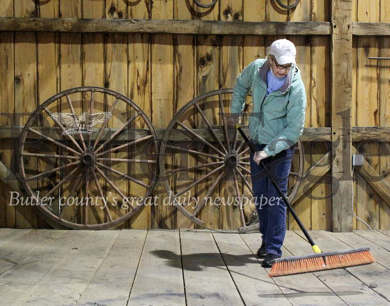 Harold Aughton/Butler Eagle: Joan Szakelyhidi, 70, of Harmony volunteered to help with the spring cleaing of the Harmonist - Ziegler Barn Friday, April 26. The original barn was built in 1805 to house the Harmonist's growing flock of sheep.