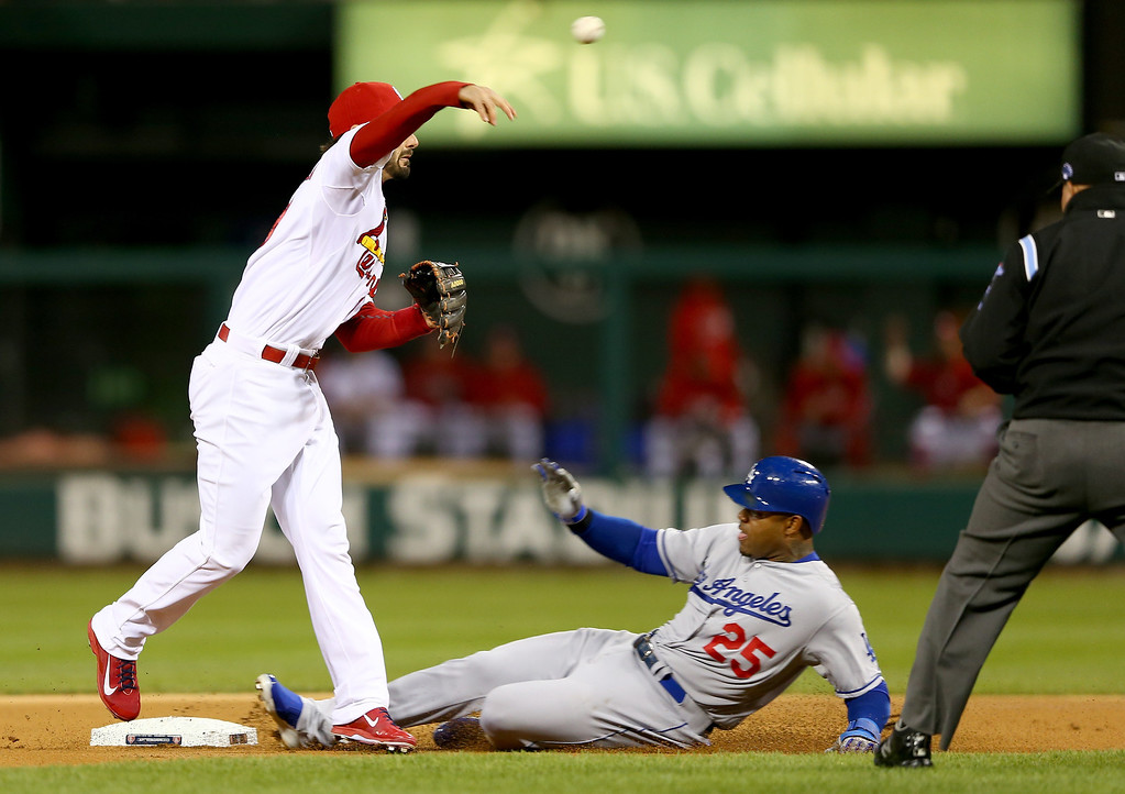 . ST LOUIS, MO - OCTOBER 18:  Matt Carpenter #13 of the St. Louis Cardinals turns a double play as Carl Crawford #25 of the Los Angeles Dodgers is out at second base in the first inning in Game Six of the National League Championship Series at Busch Stadium on October 18, 2013 in St Louis, Missouri.  (Photo by Elsa/Getty Images)