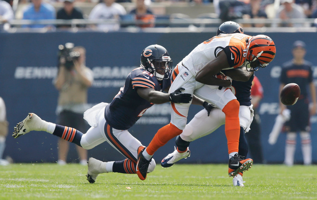 . Cincinnati Bengals wide receiver A.J. Green (18) fumbles the ball as he is tackled by Chicago Bears strong safety Major Wright (21) and cornerback Tim Jennings during the first half of an NFL football game, Sunday, Sept. 8, 2013, in Chicago. The ball went out of bounds. (AP Photo/Nam Y. Huh)
