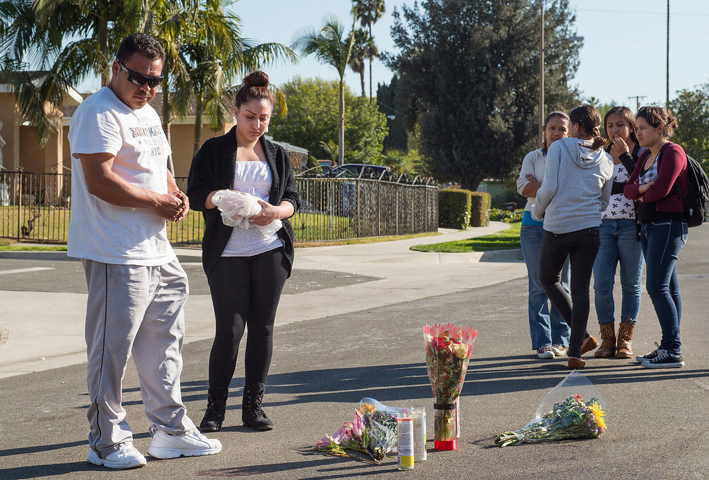 . Mourners gather to place flowers at Wickshire Avenue and Kennard Street--the scene of a hit-and-run homicide that occurred after an altercation at a house party in Hacienda Heights Feb. 25, 2013.   (SGVN/Staff photo by Leo Jarzomb)