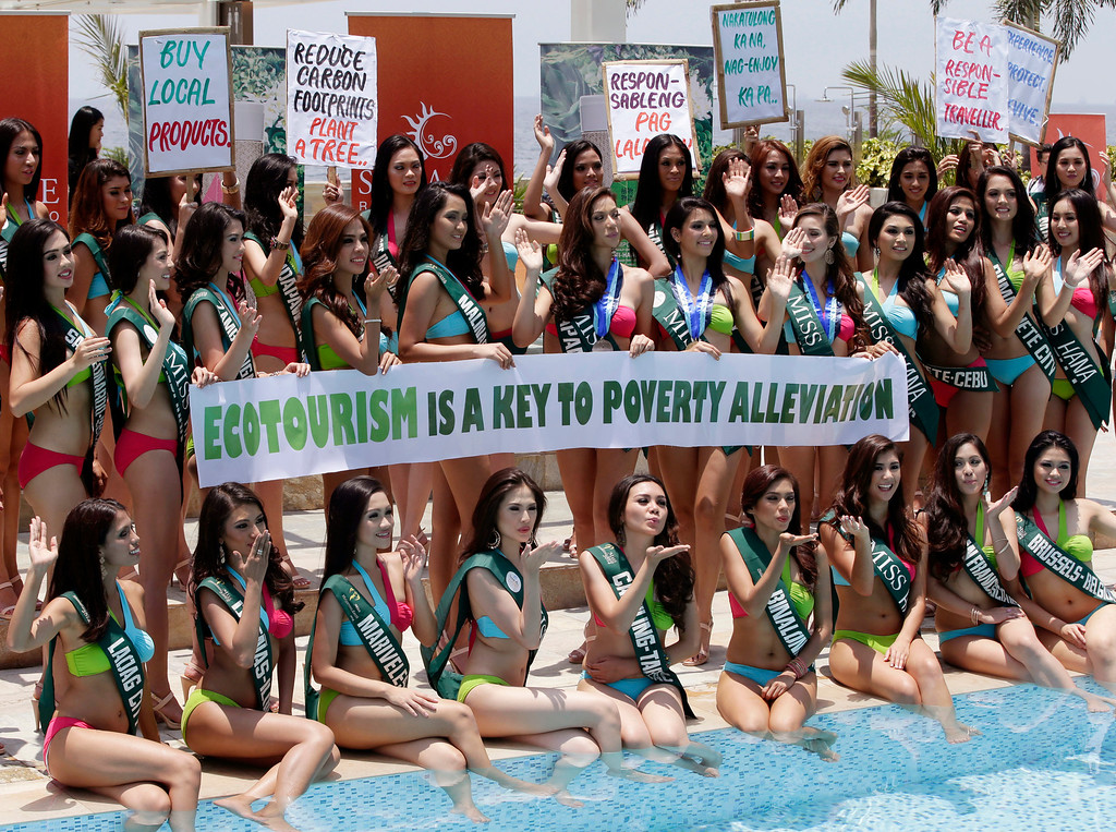 . Candidates for the Miss Earth 2014 Philippines beauty pageant display Earth Day messages Tuesday, April 22, 2014 by the poolside of a hotel-casino at suburban Pasay city, south of Manila, Philippines. Some 49 candidates are vying for the title of the only beauty pageant with a unique theme of saving Mother Earth. (AP Photo/Bullit Marquez)