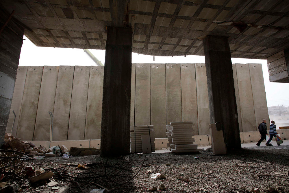. Palestinian men walk near a part of Israel\'s controversial barrier which is under construction in the Shuafat refugee camp in the West Bank near Jerusalem January 27, 2013. REUTERS/Baz Ratner