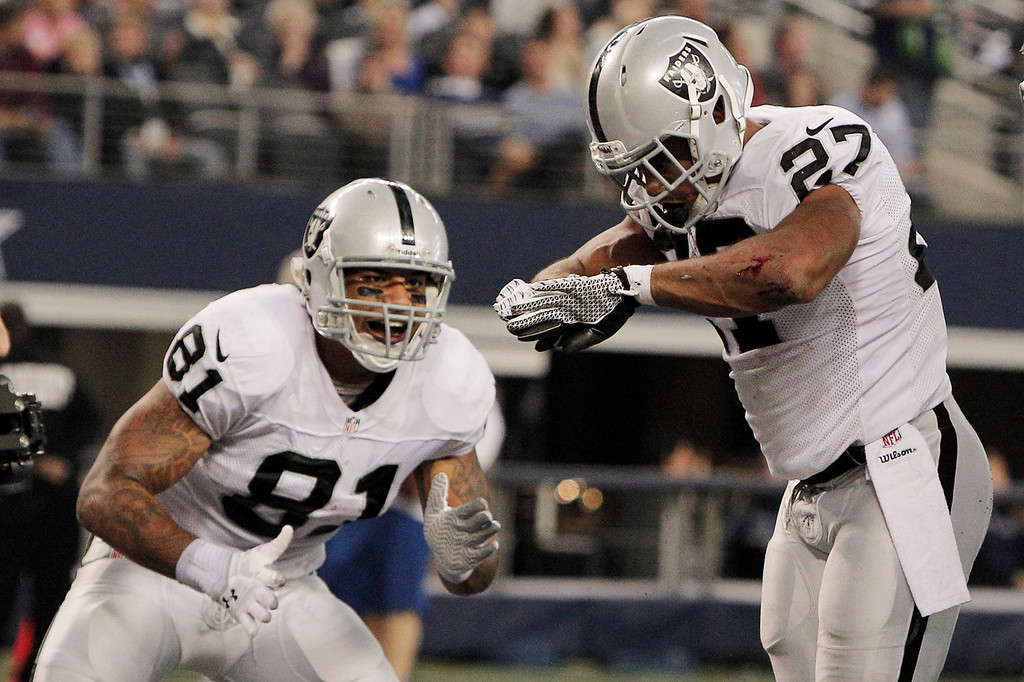 . Oakland Raiders running back Rashad Jennings (27) celebrates his touchdown against the Dallas Cowboys with Mychal Rivera during the first half of an NFL football game, Thursday, Nov. 28, 2013, in Arlington, Texas.  (AP Photo/Brandon Wade)