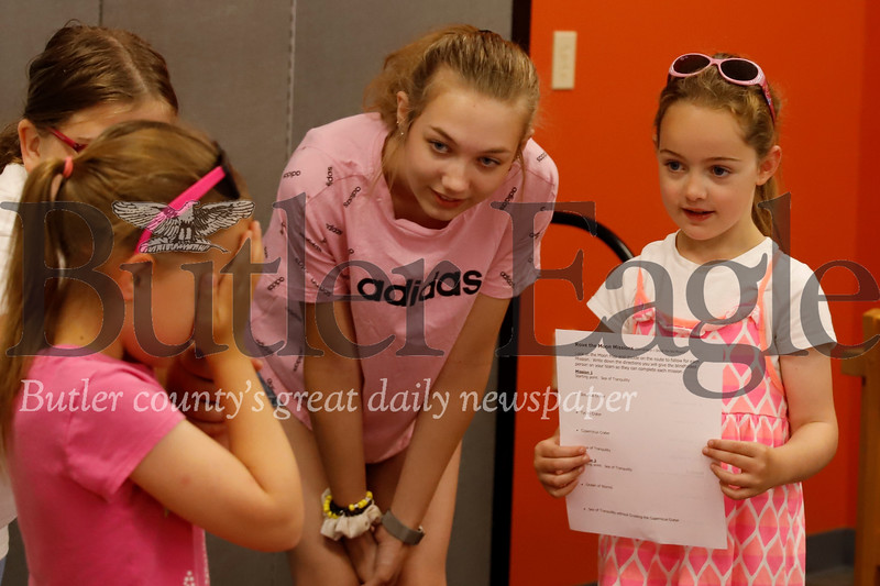 Brielle Gordon, 7, keeps her eyes closed to simulate being a moon rover while her sister Brynn gives instructions on where to go with library volunteer Brooke Lassinger, 15, Thursday. 07/25/19 Seb Foltz/Butler Eagle