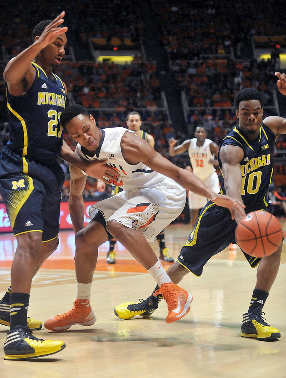 . Illinois guard Joseph Bertrand (2) loses the ball between Michigan guards Zak Irvin (21) and Derrick Walton Jr. (10) during the first half of an NCAA college basketball game Tuesday, March 4, 2014, in Champaign, Ill. (AP Photo/Rick Danzl)