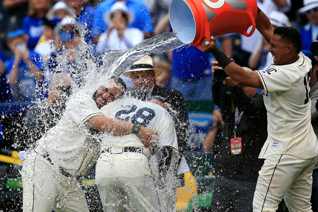 . Kansas City Royals designated hitter Kendrys Morales, left, holds on to his interpreter and catching coach Pedro Grifol (28) while getting doused by teammate Salvador Perez, right, following a baseball game against the Atlanta Braves at Kauffman Stadium in Kansas City, Mo., Sunday, May 15, 2016. The Royals defeated the Braves 4-2 in 13 innings. (AP Photo/Orlin Wagner)