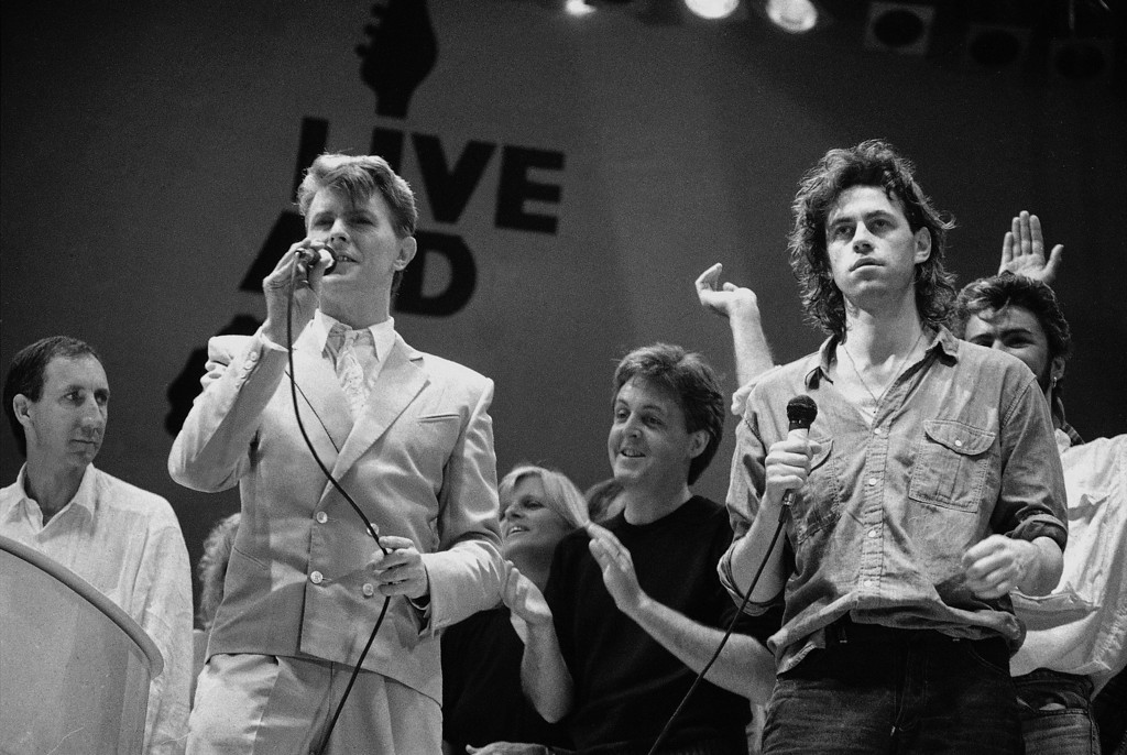. FILE - This is a Saturday, July 13, 1985 file photo of  David Bowie, front left, and Bob Geldof, right right, at the end of the London part of the Live Aid famine relief concert at Wembley Stadium in London. Bowie, the other-worldly musician who broke pop and rock boundaries with his creative musicianship, nonconformity, striking visuals and a genre-bending persona he christened Ziggy Stardust, died of cancer Sunday Jan. 10, 2016. He was 69 and had just released a new album. (AP Photo/Joe Schaber, File)