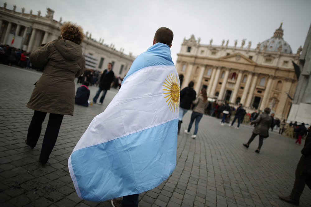 . A boy walks in St Peter\'s Square wrapped in the flag of Argentina before Pope Francis gave his first Angelus blessing on March 17, 2013 in Vatican City, Vatican. The Vatican is preparing for the inauguration of Pope Francis on March 19, 2013 in St Peter\'s Square.  (Photo by Dan Kitwood/Getty Images)