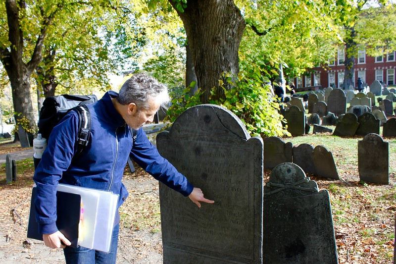 Context Travel tour guide points out bullet holes on a tombstone in Copp's Hill Burying Ground in Boston's North End