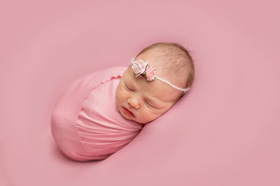 Colour studio photograph of newborn baby girl, wrapped in pink against a pink backdrop