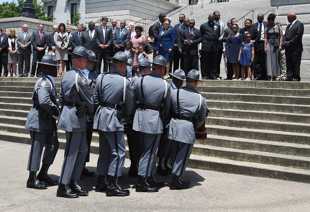 . A South Carolina Highway Patrol honor guard carries the casket of Sen. Clementa Pinckney to the Statehouse, Wednesday, June 24, 2015, in Columbia, S.C. Pinckney\'s open coffin was put on display under the dome where he served the state for nearly 20 years. He was one of those killed in a mass shooting at the Emanuel AME Church in Charleston. (AP Photo/Rainier Ehrhardt)