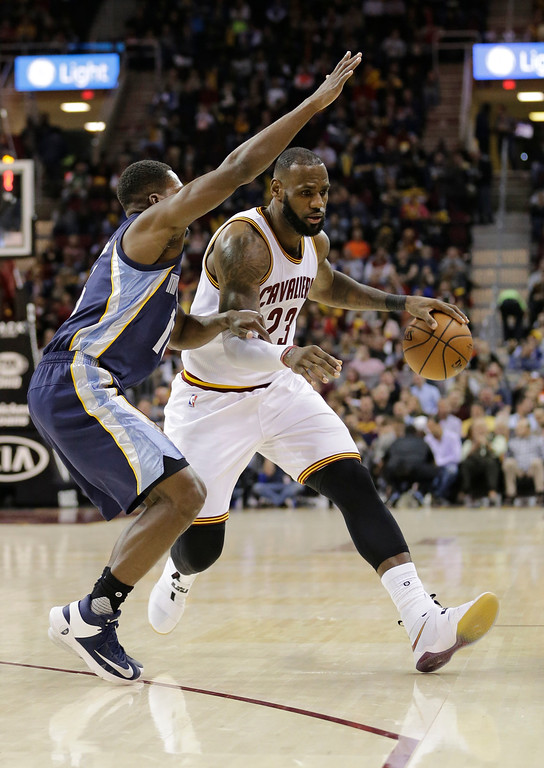 . Cleveland Cavaliers\' LeBron James, right, drives past Memphis Grizzlies\' Toney Douglas in the first half of an NBA basketball game Tuesday, Dec. 13, 2016, in Cleveland. (AP Photo/Tony Dejak)