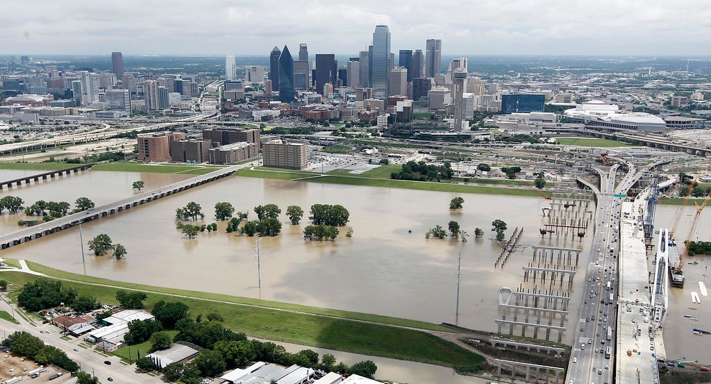. Motorists commute across Interstate 30, right, over a swollen Trinity River west of downtown Dallas, Friday, May 29, 2015. Floodwaters submerged Texas highways and threatened more homes Friday after another round of heavy rain added to the damage inflicted by storms. (AP Photo/Brandon Wade)