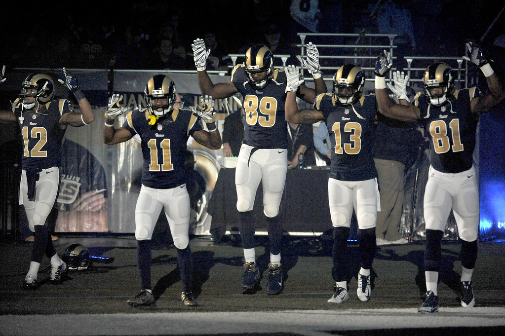 . FILE - In this Sunday Nov. 30, 2014, file photo, St. Louis Rams players, from left; Stedman Bailey (12), Tavon Austin (11), Jared Cook, (89) Chris Givens (13) and Kenny Britt (81) raise their arms in awareness of the events in Ferguson, Mo.,  as they walk onto the field during introductions before an NFL football game against the Oakland Raiders in St. Louis. Time will tell whether the ``hands-up\'\' gesture during pregame introductions will leave a lasting memory or simply go down as a come-and-go moment in the age of the 24-hour news cycle. Either way, it certainly isn\'t the first time high-profile athletes have used their platform to make political statements. (AP Photo/L.G. Patterson, File)