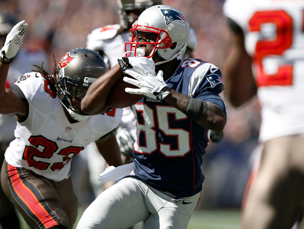 . New England Patriots wide receiver Kenbrell Thompkins (85) runs past Tampa Bay Buccaneers strong safety Mark Barron (23) for a touchdown after catching a Tom Brady pass the in the first half of an NFL football game Sunday, Sept. 22, 2013, in Foxborough, Mass. (AP Photo/Elise Amendola)