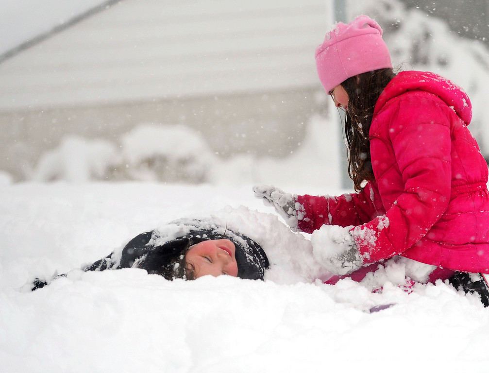 . Ashton Lam, left, 8, is buried in the snow by friend Ava Miller, 10, as they enjoy the winter weather in Staunton, Va, on Wednesday, March 6, 2012. The March snowstorm is primarily hitting a region stretching from central Virginia to the northern and western portions of the state, where snow is piling up quickly. (AP Photo/The News Leader, Mike Tripp)