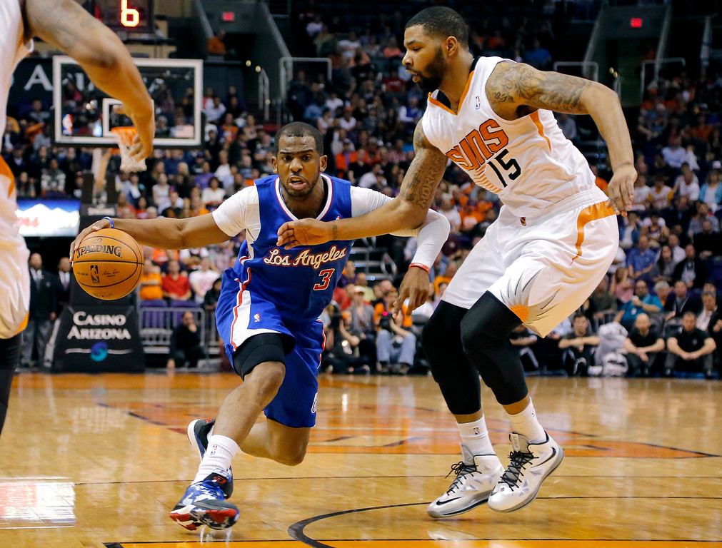 . Los Angeles Clippers guard Chris Paul (3) drives as Phoenix Suns forward Marcus Morris (15) defends during the first half of an NBA basketball game on Wednesday, April 2, 2014, in Phoenix. (AP Photo/Matt York)
