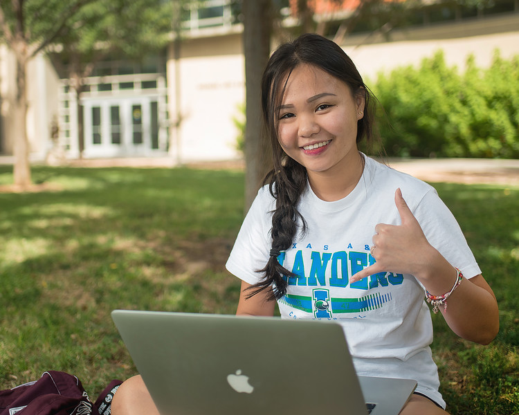 Student Susie Nguyen throws a shaka as she studies for her international business class.