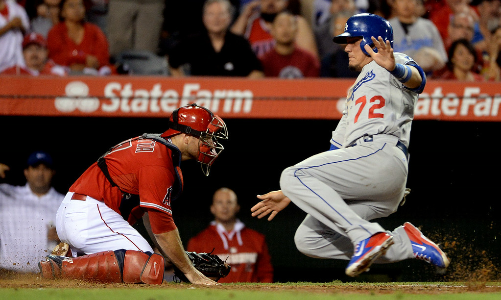 . Los Angeles Dodgers\' Miguel Rojas (72) scores past Los Angeles Angels catcher Chris Iannetta (17) on a RBI sinlge by Adrian Gonzalez (not pictured) in the eighth inning of a baseball game at Anaheim Stadium in Anaheim, Calif., on Thursday, Aug. 7, 2014.  (Photo by Keith Birmingham/ Pasadena Star-News)