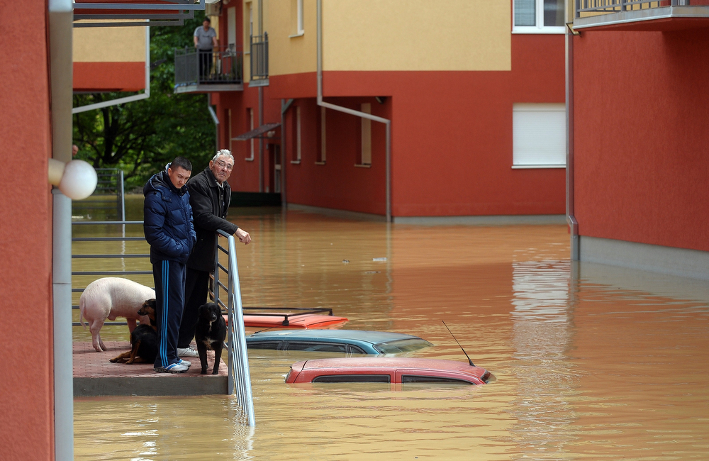 . People wait for evacuation in front of their flooded house in the town of Obrenovac, 40 kilometers west of Belgrade, on May 17, 2014. Deadly floods across Bosnia and Serbia have claimed at least 14 lives and led to the evacuation of 15,000 people after the Balkans suffered its heaviest rainfall in a century, officials said on Saturday.  (ALEXA STANKOVIC/AFP/Getty Images)