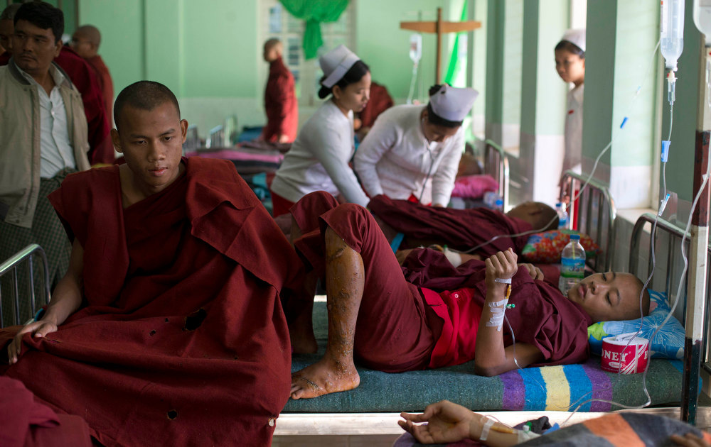 Description of . Buddhist monks with burn injuries are treated at a hospital in Monywa, northwestern Myanmar, Thursday, Nov. 29, 2012. Security forces cracked down on protesters occupying a copper mine early Thursday, using water cannons and other devices to break up the rally hours before opposition leader Aung San Suu Kyi was expected to hear their grievances. Unexplained fires engulfed the protest camps at the Letpadaung mine in northwestern Myanmar and dozens of Buddhist monks and villagers were injured, according to several protesters. (AP Photo/Gemunu Amarasinghe)