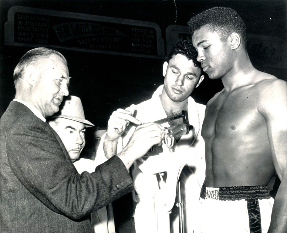 . Alejandro Lavorante, Argentine heavyweight, lends a helping hand to Clayton Frye, secretary of the California Athletic Commission, as he weighs Cassius Clay of Louisville, Ky., for their 10-round fight in the Los Angeles Sports Arena tonight.  Clay weighed 199 pounds to Lavorante\'s 208. 1962. Credit: AP