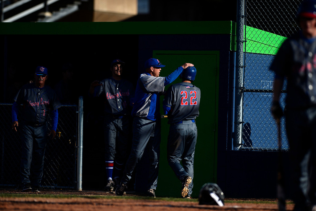 . Aurora, CO - APRIL 08: Parker Jax (22) of the Cherry Creek Bruins is greeted in the dugout after scoring the go-ahead run against the Overland Trailblazers. Overland hosted Cherry Creek on Tuesday, April 8, 2014. (Photo by AAron Ontiveroz/The Denver Post)