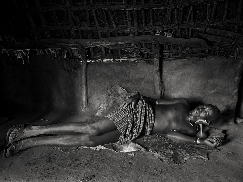 Hamar man sleeping in his hut. Hamar men can often be seen carrying a little wooden stool which they use for sitting when away from home or as a pillow when sleeping. The bed comes in the form of a very thin Cowhide which they roll away during the day. 