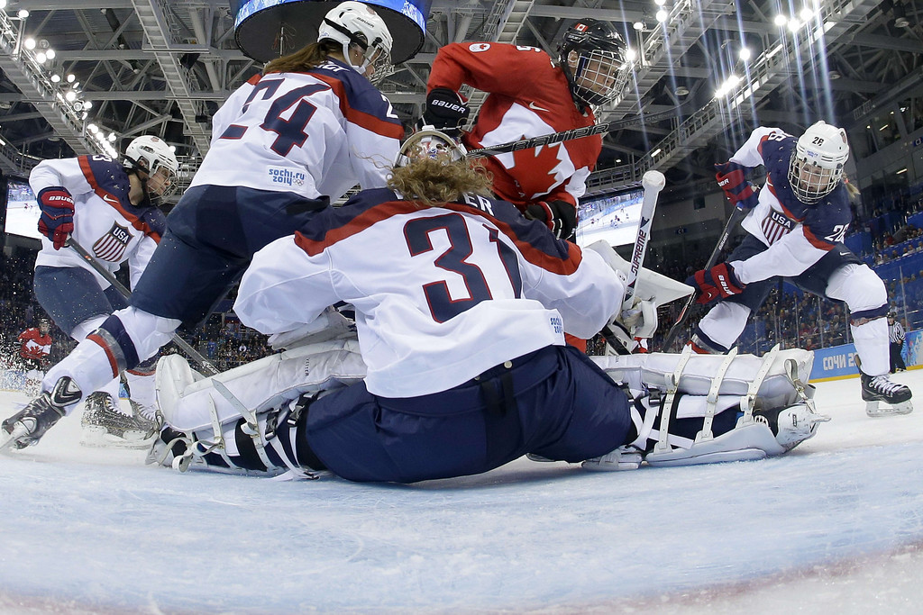 . Canada\'s Rebecca Johnston (C) vies with US players during the Women\'s Ice Hockey Group A match between Canada and USA at the Sochi Winter Olympics on February 12, 2014 at the Shayba Arena. AFP PHOTO / POOL / MATT  SLOCUM/AFP/Getty Images