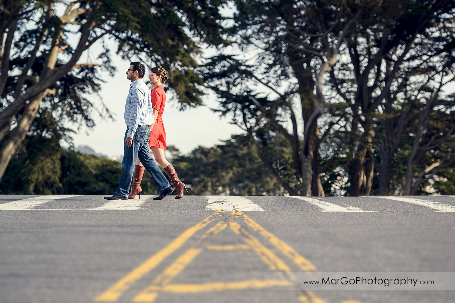 man in blue shirt and woman in red dress holding hands and walking thoruh the crossing during engagement session at San Francisco Legion of Honor