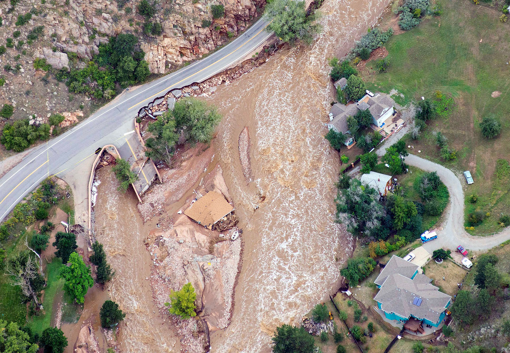 . Homes are cut off from a nearby road in Lyons, Colo., as flooding continues to devastate the Front Range and thousands are forced to evacuate with an unconfirmed number of structures destroyed Friday, Sept. 13, 2013. (AP Photo/John Wark)