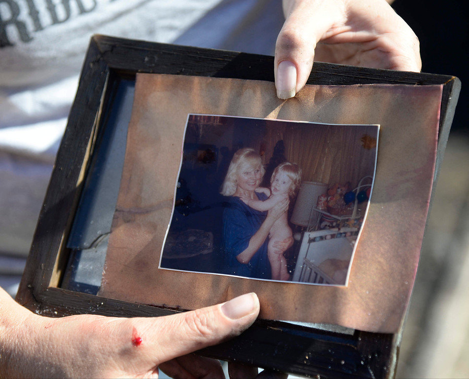. Local neighbor and close friend Michelle Lesser finds a photo of her friend after she was killed in a house fire Saturday night in Burbank. The fire was reported at about 9:20 p.m. Saturday at 910 North Evergreen St.  Flames were showing when firefighters arrived with three people were in the house when the fire broke out. One person died in the fire, but two people got out and were transported to a hospital with non-life threatening injuries. Oct 20, 2013. Burbank CA. Photos by Gene Blevins/LA Daily News