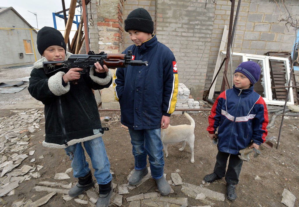 ". Boys play with an unloaded submachine gun which was given to them by Ukrainian servicemen in the village of Chermalyk, some 40 km north-east of the eastern Ukrainian port of Mariupol, in the region of Donetsk on February 26, 2015. The Ukraine\'s military said it was starting the withdrawal of heavy weapons from the frontline with pro-Russian rebels, a key step in a stuttering peace plan. ""Ukraine is beginning the withdrawal of 100mm cannons from the frontline. GENYA SAVILOV/AFP/Getty Images"