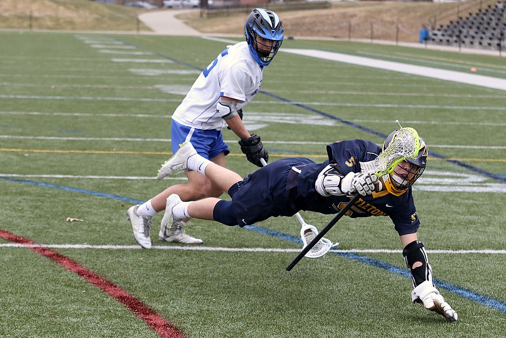 . Leominster High School boys lacrosse played Littleton High School today at Doyle Field in Leominster. Leominster\'s Gaetano Dandini  watches as Littleton\'s William Scott goes flying as he tries to hold onto the ball. SENTINEL & ENTERPRISE/JOHN LOVE