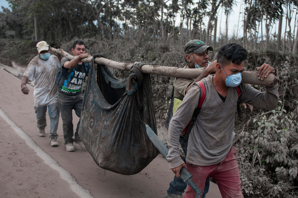 ". Residents carry a body recovered near the Volcan de Fuego, or ""Volcano of Fire,\"" in Escuintla, Guatemala, Monday, June 4, 2018. A fiery volcanic eruption in south-central Guatemala sent lava flowing into rural communities Sunday, killing several people. Rescuers struggled to reach people where homes and roads were charred and blanketed with ash. (AP Photo/Oliver de Ros)"