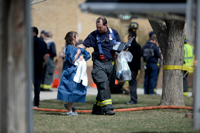 . A student is dressed in a gown after being showered during an evacuation after students were exposed to hazardous skin irritants. Jeffco Open School evacuation on Monday, April 8, 2014. (Photo by AAron Ontiveroz/The Denver Post)