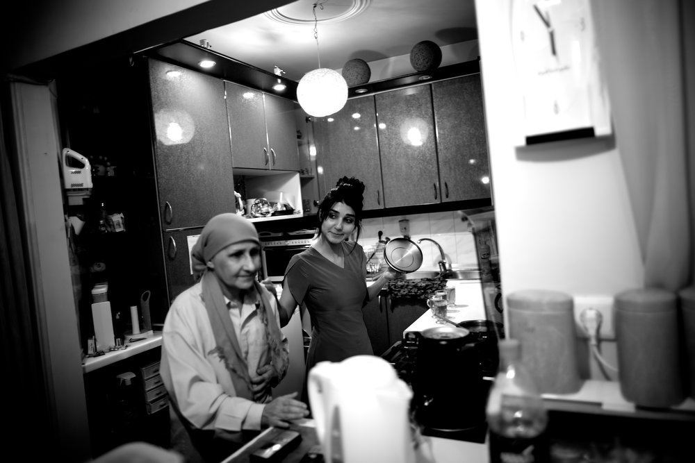 . Soheila Mehri (L), who suffers from breast cancer, checks food prepared by her daughter Sara at their house in Tehran on March 3, 2013, when she was feeling better and was able to walk again.  AFP PHOTO/BEHROUZ MEHRI