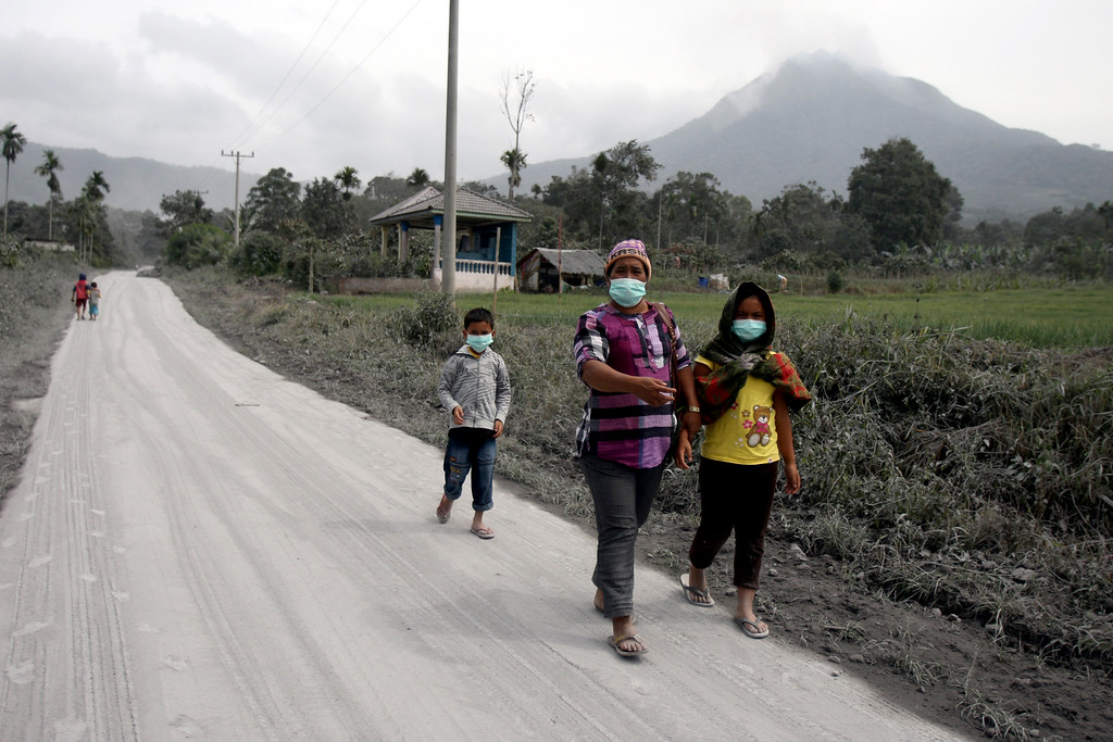 . Villagers walk on a road covered with volcanic ash from the eruption of Mount Sinabung, background, in Tiga Nderket, North Sumatra, Indonesia, Tuesday, Nov. 5, 2013.  (AP Photo/Binsar Bakkara)