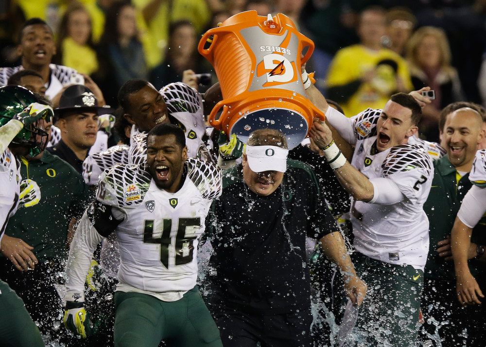 Description of . Michael Clay #46 and Bryan Bennett #2 dump the gatorade cooler on head coach Chip Kelly of the Oregon Ducks after their 35 to 17 victory over the Kansas State Wildcats in the Tostitos Fiesta Bowl at University of Phoenix Stadium on January 3, 2013 in Glendale, Arizona.  (Photo by Ezra Shaw/Getty Images)