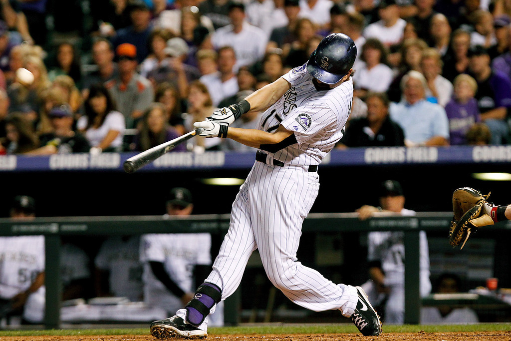 . Colorado Rockies\' Todd Helton hits a three-run home run on a pitch by Cincinnati Reds\' Bronson Arroyo during the fourth inning of a baseball game, Friday, Aug. 30, 2013, in Denver. (AP Photo/Barry Gutierrez)