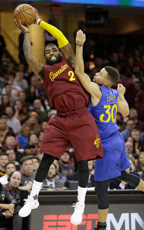 . Cleveland Cavaliers\' Kyrie Irving (2) passes over Golden State Warriors\' Stephen Curry (30) in the first half of an NBA basketball game, Sunday, Dec. 25, 2016, in Cleveland. (AP Photo/Tony Dejak)