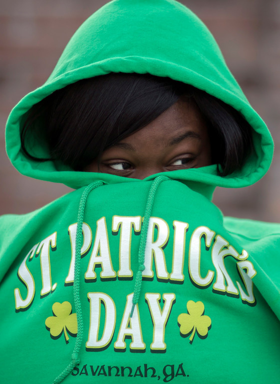 . Chizzy Odimgbe keeps warm before the start of the St. Patrick\'s Day parade, Tuesday, March 17, 2015, in Savannah, Ga. The St. Patrick\'s Day tradition in Savannah dates back to the first parade held on March 17, 1824. While Savannah has been celebrating St. Patrick\'s Day for 191 years, there have been at least six years without a parade. (AP Photo/Stephen B. Morton)