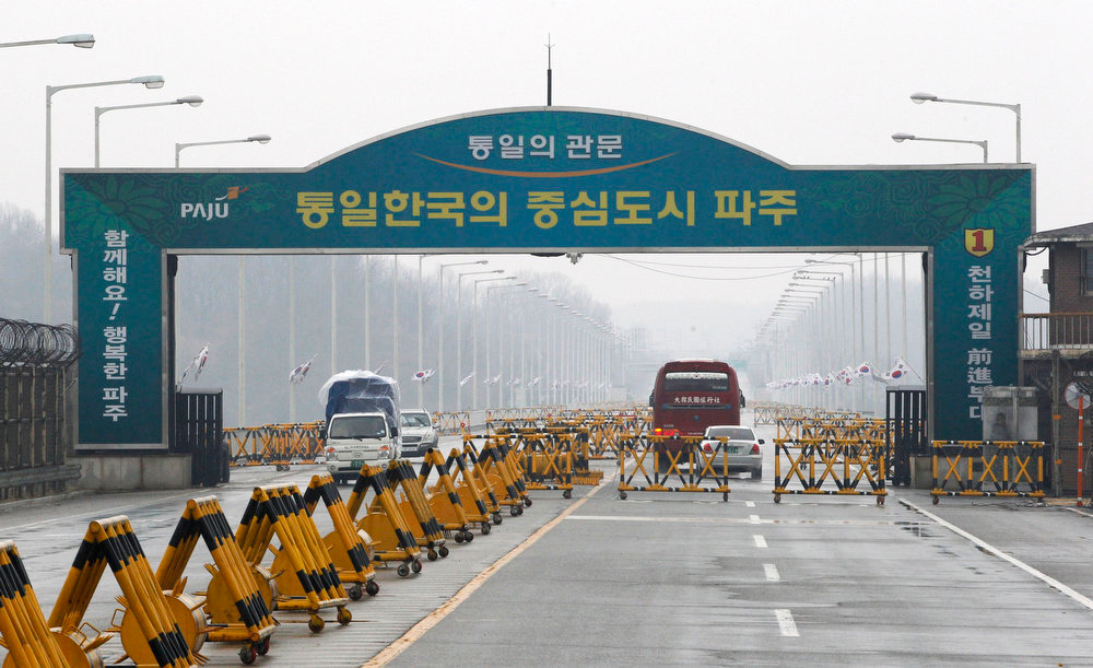 ". South Korean vehicles, left, return from the North Korean city of Kaesong at Unification Bridge in Paju, South Korea, near the border village of Panmunjom, Saturday, April 6, 2013. More South Koreans on Saturday began to leave North Korea and the factory park where they work, four days after Pyongyang closed the border to people and goods. The letters read "" Unification Gate.\"" (AP Photo/AhnnYoung-joon)"