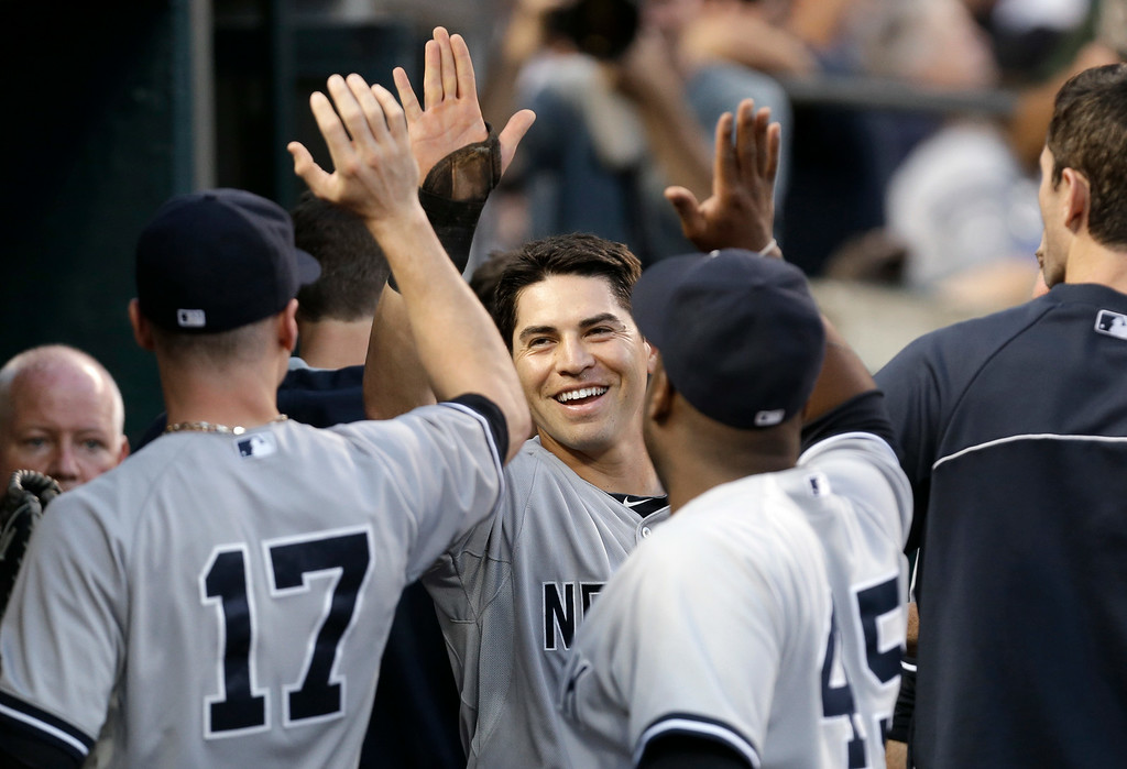 . New York Yankees\' Jacoby Ellsbury, center, celebrates after scoring on a Derek Jeter double against the Detroit Tigers in the third inning of a baseball game in Detroit Wednesday, Aug. 27, 2014. (AP Photo/Paul Sancya)