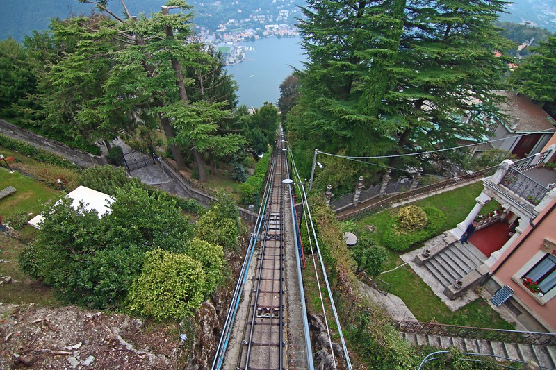 an aerial view of a funicular going down towards a lake