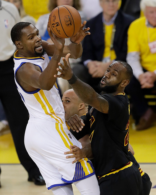 . Golden State Warriors forward Kevin Durant, left, passes against Cleveland Cavaliers forward LeBron James during the first half of Game 5 of basketball\'s NBA Finals in Oakland, Calif., Monday, June 12, 2017. (AP Photo/Marcio Jose Sanchez)
