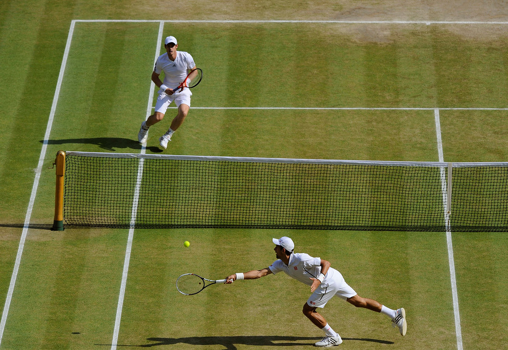 . Novak Djokovic of Serbia, front, plays a return to Andy Murray of Britain during the Men\'s singles final match at the All England Lawn Tennis Championships in Wimbledon, London, Sunday, July 7, 2013. (AP Photo/Tom Hevezi, Pool)