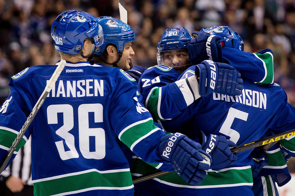 . From left, Vancouver Canucks\' Jannik Hansen, Kevin Bieksa, Chris Higgins and Jason Garrison celebrate Garrison\'s goal against the Colorado Avalanche during the first period of an NHL hockey game in Vancouver, British Columbia, on Wednesday, Jan. 30, 2013. (AP Photo/The Canadian Press, Darryl Dyck)