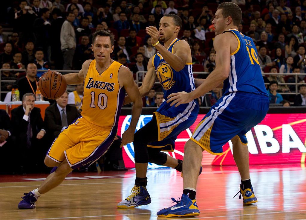 . Steve Nash of the LA Lakers, left, drives to the basket with the ball against Stephen Curry, center, and David Lee, right, of the Golden State Warriors during their NBA Global Game at the Wukesong Stadium in Beijing, Tuesday, Oct. 15, 2013.  (AP Photo/Andy Wong)